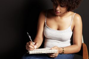 african woman is writing in a dark room